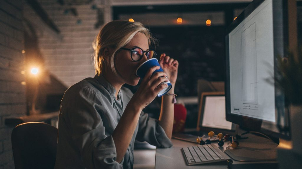 Woman drinking coffee in front of computer in the dark