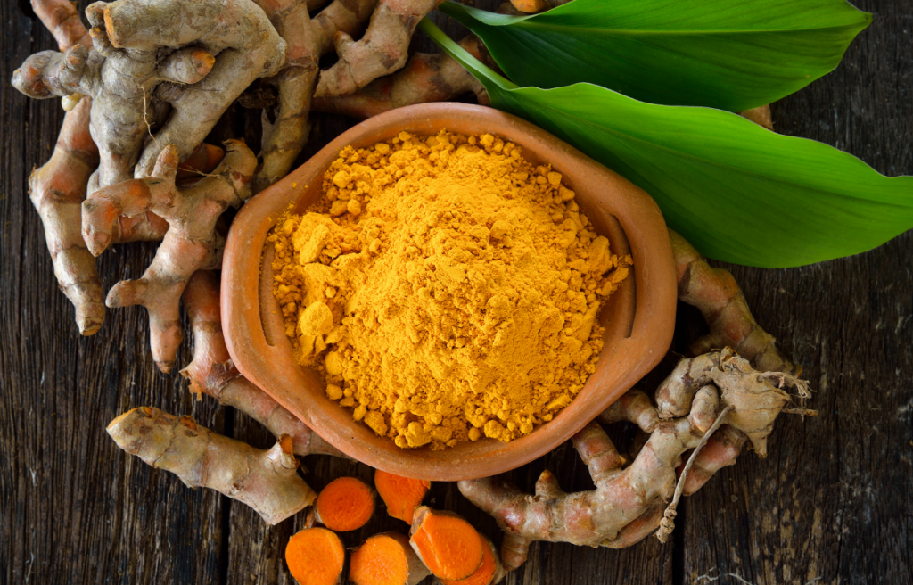 Ground turmeric in bowl on a table with turmeric root and leaves